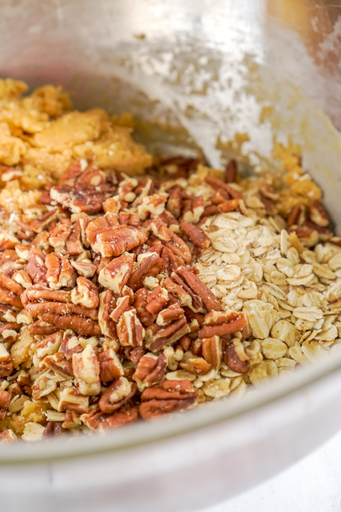 Rolled oats and pecans added to bowl